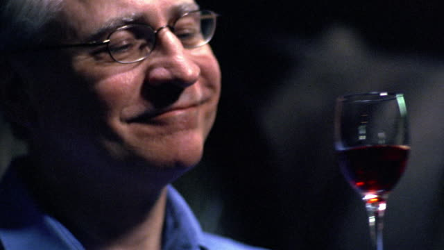 close up man in eyeglasses examining, smelling + tasting glass of red wine + smiling / Porto, Portugal