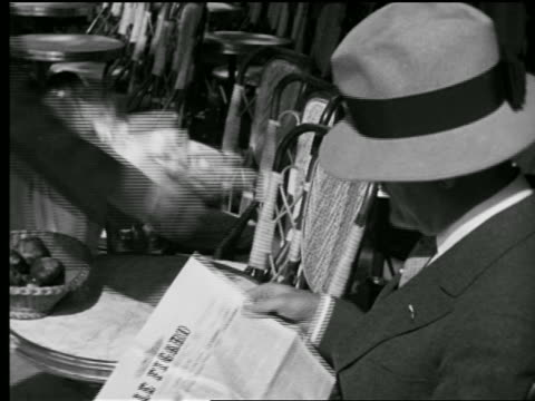 """B/W 1927 close up man in hat at table in sidewalk cafe reading """"Le Figaro"""" / waiter brings cups / Paris"""