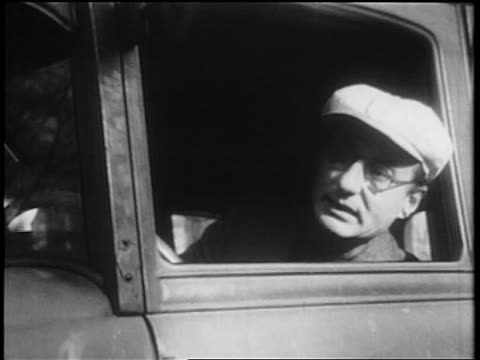 B/W 1939 close up man in hat + eyeglasses looking out car window + shouting / documentary