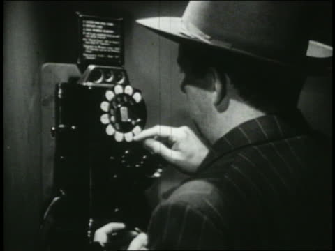 b/w 1949 rear view close up man in hat using pay phone - 電話ボックス点の映像素材/bロール