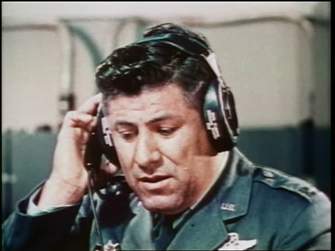 close up man in military uniform talking into headset / control room / cold war / documentary - dejaover点の映像素材/bロール