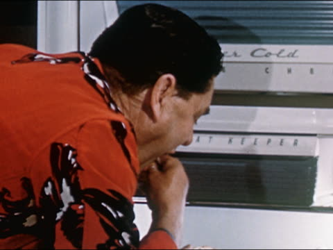 1951 Close up man in robe eating turkey from fridge at night while looking over shoulder / AUDIO