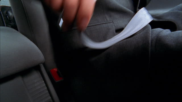 vidéos et rushes de close up man in suit fastening seat belt - ceinture de sécurité