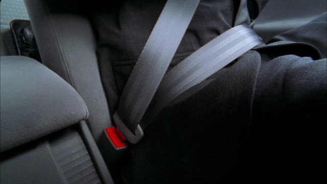 vidéos et rushes de close up man in suit unfastening seat belt - ceinture de sécurité