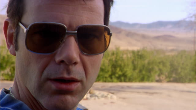 Close up man in sunglasses turning to CAM and smiling