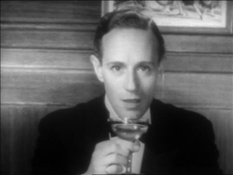 b/w 1934 close up man in tuxedo with champagne glass (leslie howard) talking towards camera / feature - 1934 stock-videos und b-roll-filmmaterial