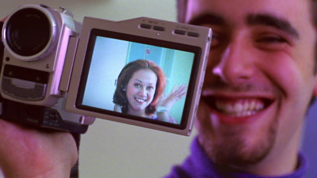 close up man laughing holding video camera with woman in viewfinder screen waving to camera