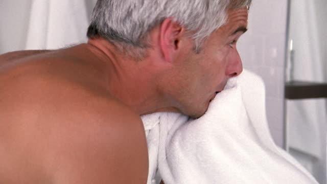 vídeos y material grabado en eventos de stock de close up man leaning over sink and mirror in bathroom + drying face w/towel / reflection of man in mirror - vello pectoral