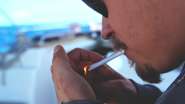 4k schließen sich der mensch licht und rauchen zigarette auf segelboot, real-time - smoking stock-videos und b-roll-filmmaterial