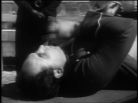 B/W 1937 close up man lying on table stuffing tube in mouth / man + woman in background