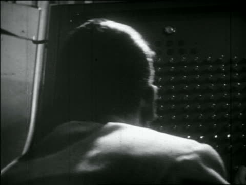 b/w 1956 close up man operating panel with lights / pan man working on large telegraph machine - telegraph machine stock videos and b-roll footage