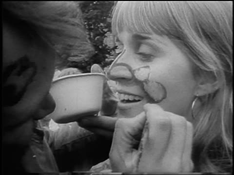 vídeos de stock e filmes b-roll de b/w 1967 close up man painting blonde woman's face outdoors at bein / provincetown / newsreel - love in