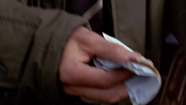 vídeos de stock e filmes b-roll de close up man paying other man in euros bills / ireland - 2002