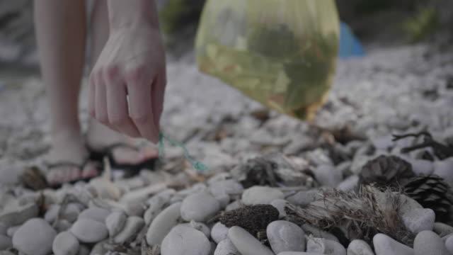 vídeos y material grabado en eventos de stock de close up, man picks up trash on hvar beach - cultura croata