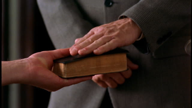 Close up man placing hand on Bible / tilt up to middle aged man saying oath