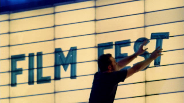 close up man placing letters on movie theater marquee / seattle, washington - film premiere stock videos and b-roll footage