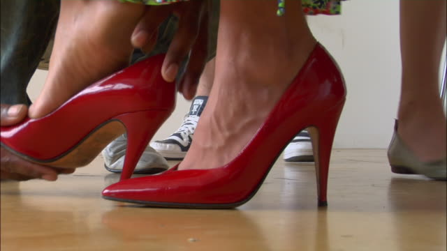 Close up man placing models foot in red high-heeled shoe / dusting off shoe