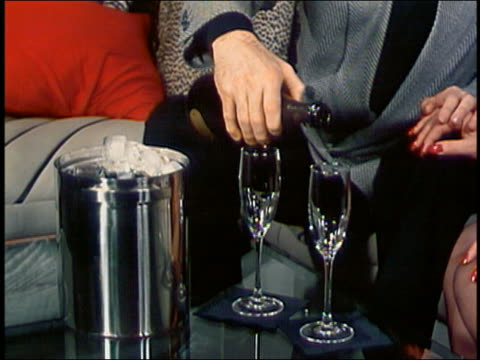 vídeos de stock e filmes b-roll de close up man pouring champagne into two glasses w/one hand / holding woman's hand w/other / drinking - balde de gelo