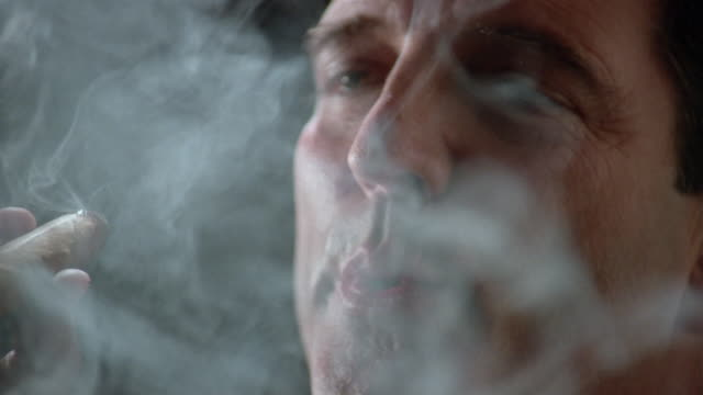 close up man puffing on cigar, looking at camera and smiling - excess stock videos and b-roll footage
