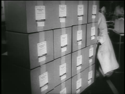 close up man pushing cart with stacks of boxes of polio vaccine / newsreel - polio stock videos & royalty-free footage