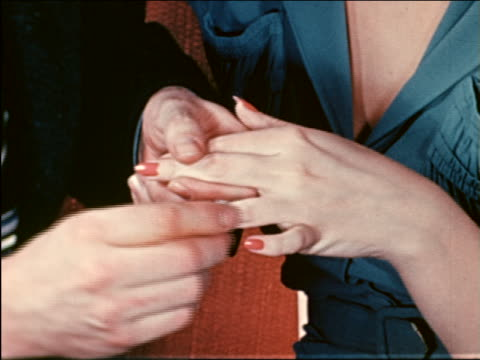 1941 close up man putting engagement ring on finger of woman / industrial