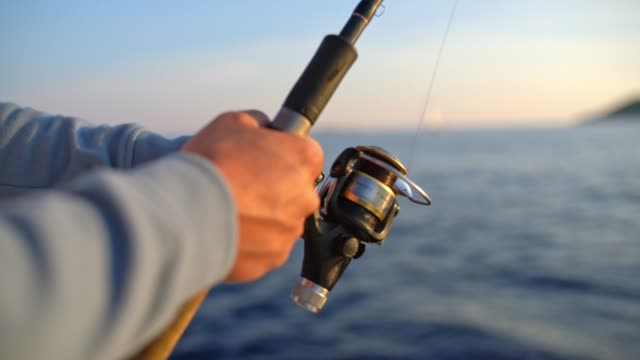 4k close up man reeling in fishing line, real time - fishing rod stock videos & royalty-free footage