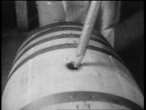 b/w 1932 close up man removing pipe from barrel / 2nd man taking whiskey sample / louisville ky - destillation stock-videos und b-roll-filmmaterial