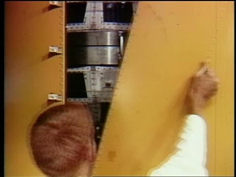 1962 close up man removing yellow panel to reveal telstar satellite - telstar stock-videos und b-roll-filmmaterial