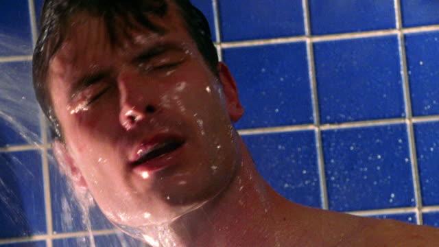 vídeos de stock e filmes b-roll de close up man rinsing face + hair in shower - homem tomando banho