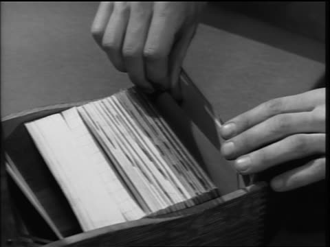 B/W 1951 OVERHEAD close up man' s hands searching through card file + pulling cards / The Right Slant