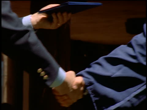 close up man shaking hands with male graduate + giving him diploma