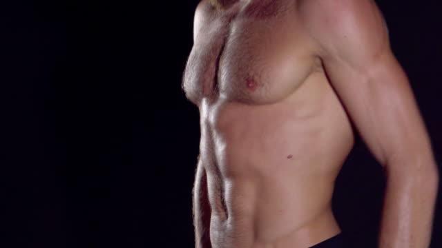 vídeos de stock, filmes e b-roll de feche o homem mostrando um fisiculturista de homem perfeito abs muscular. homem posando em um fundo preto, mostra os seus músculos. musculação, posando, fundo preto, músculos - o conceito de musculação. - braço
