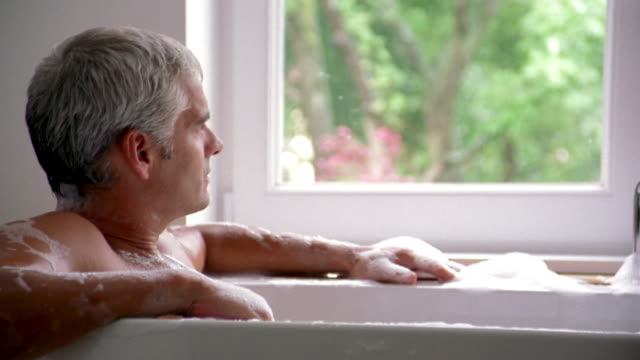 close up man sitting in bathtub looking out window w/view of trees - bubble bath stock videos and b-roll footage