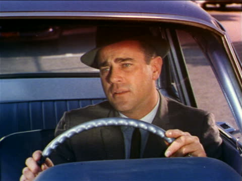 1962 close up man sitting in driver's seat of car looking disappointed / industrial - tristezza video stock e b–roll