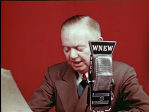 1945 close up man speaking into wnew radio microphone / red background / industrial - presenter stock videos & royalty-free footage