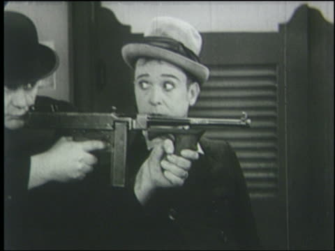 vídeos de stock e filmes b-roll de b/w 1933 close up man (harry langdon) stares at man with machine gun + prepares to hit him - gânguester
