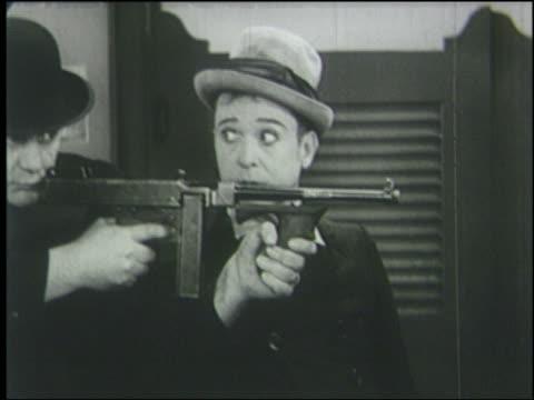 B/W 1933 close up man (Harry Langdon) stares at man with machine gun + prepares to hit him