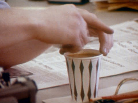 vidéos et rushes de 1970 close up man stirring coffee in paper cup next to newspaper lying on desk - 1970