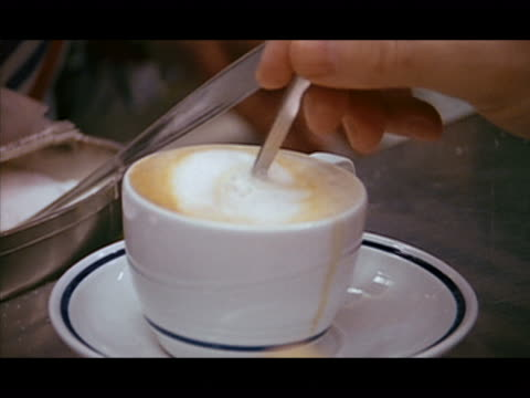 Close up man stirring cup of cappucino or cafe latte / putting spoon down, picking up cup and  drinking