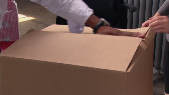Close up man taking tape off box in office/ tilt up pan man throwing tape and looking in box/ Brooklyn, New York