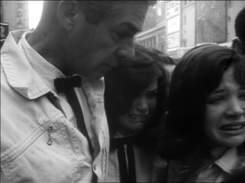 b/w 1963 close up man two women crying outdoors after john kennedy's assassination / newsreel - attentat auf john f. kennedy stock-videos und b-roll-filmmaterial