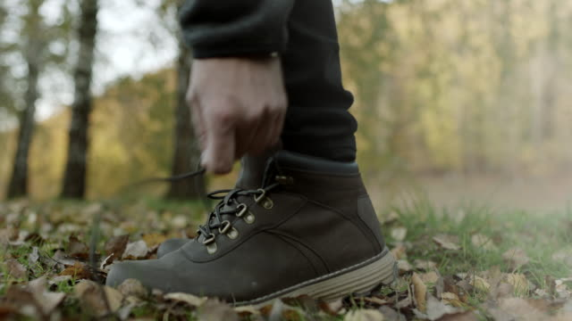 close up, man tying shoelaces on autumnal leaves - human foot stock videos and b-roll footage