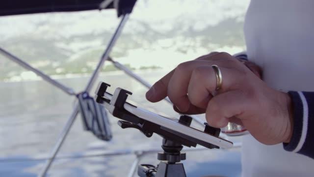 vídeos de stock, filmes e b-roll de 4k perto cara usando equipamentos de navegação digital tablet em veleiro, tempo real - software de computador