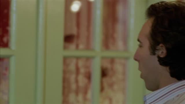 close up man walking up to door and knocking/ woman peering through door/ opening door + pulling man inside - boyfriend点の映像素材/bロール