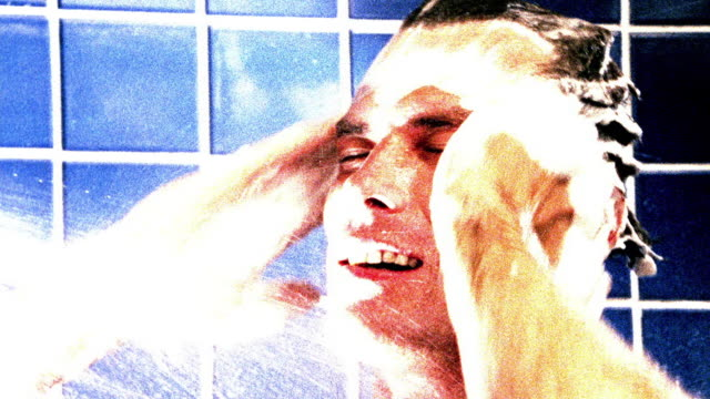 overexposed close up man washing hair in shower - shampoo per capelli video stock e b–roll