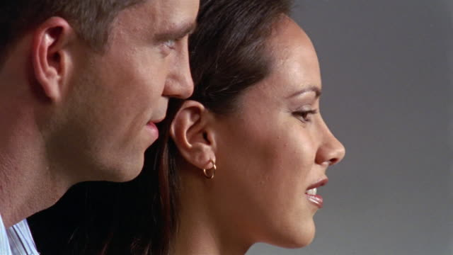 Close up man whispering into woman's ear