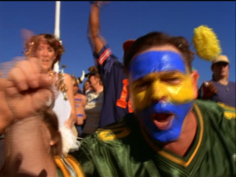 "close up man with blue + yellow face paint shouting + making ""#1"" gesture in crowded stadium - hooligan stock videos & royalty-free footage"
