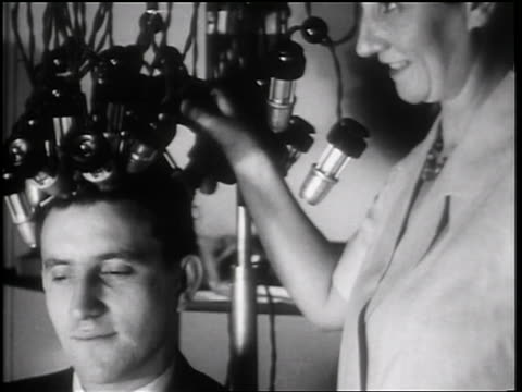 b/w 1931 close up man with curlers in hair sitting in beauty shop by female hairdresser / toledo, oh / news. - 1931 stock videos & royalty-free footage