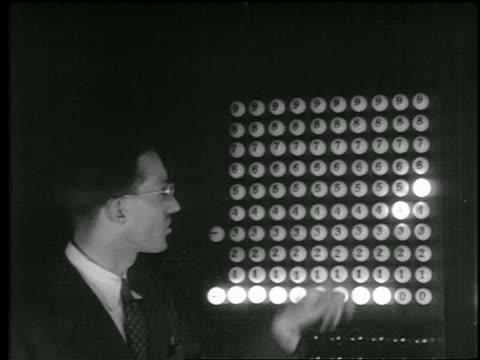 vídeos de stock e filmes b-roll de close up man with eyeglasses standing next eniac computer as numbers light up / u. of pennsylvania - 1946
