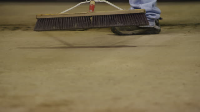 close up man with large broom sweeps the concrete floor of a machine shop. - sweeping stock videos & royalty-free footage